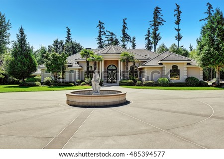 Suburban family house with fountain statue in the front yard, asphalt driveway. Luxury residential house with large windows, trees around and blue sky background. Northwest, USA