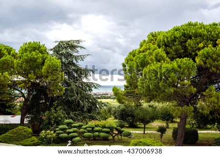Suburban flowered garden with paths in Chinese style and decorative small house. - stock photo