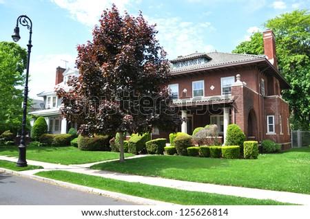 Suburban Gable Front Style Home Residential Neighborhood Sunny Blue Sky Clouds Street - stock photo