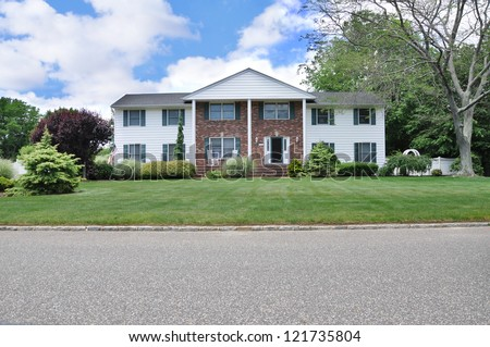 Suburban Georgian Style Home with landscaped front yard lawn in residential neighborhood American Flag