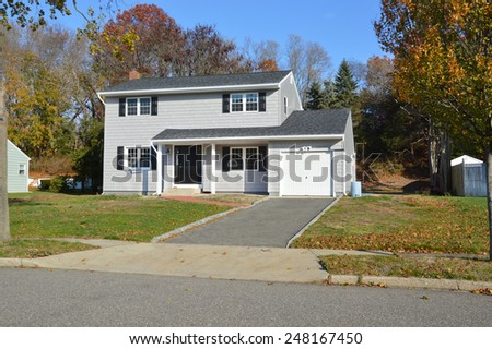 Suburban Gray High Ranch home autumn day residential neighborhood clear blue sky day USA - stock photo