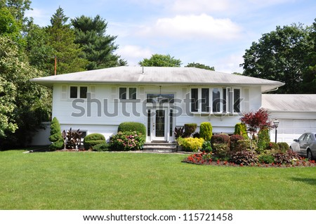 Suburban High Ranch Style Home Landscaped with flowers plants shrubs bushes sunny blue sky day - stock photo