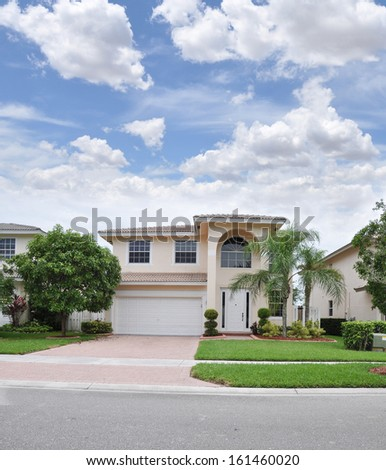 Suburban Home Brick Driveway Landscaped Lawn Palm Trees Blue Sky Clouds USA Residential Neighborhood
