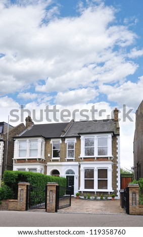 Suburban Home in London United Kingdom Europe residential neighborhood blue sky day with clouds - stock photo