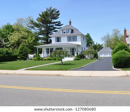 Suburban Home with Blacktop Driveway Sunny Blue Sky Day - stock photo