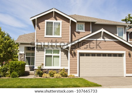 Suburban home with front porch,garage and blue sky