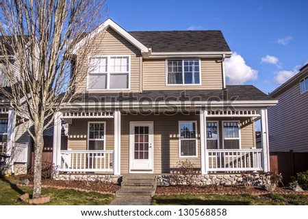 Suburban home with front porch,garage and blue sky - stock photo