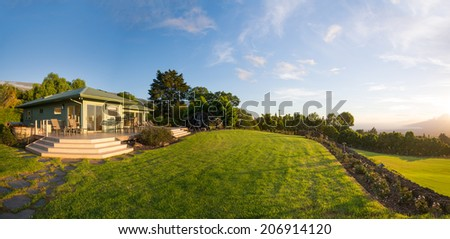 Suburban home with garden and green grassy lawn - stock photo