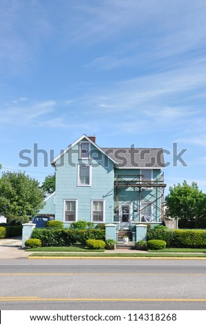 Suburban Home with scaffold equipment for repair work on House - stock photo