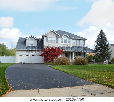 Suburban McMansion style home autumn day residential neighborhood blue sky clouds USA - stock photo