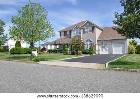 Suburban McMansion style Home Landscaped Freshly Cut Lawn Residential Neighborhood Sunny Blue Sky Day - stock photo