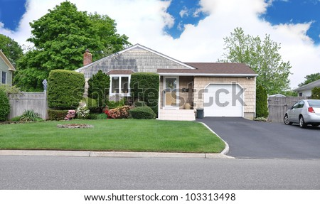 Suburban Middle Class Home Landscaped front yard lawn driveway residential neighborhood cloudy blue sky day - stock photo