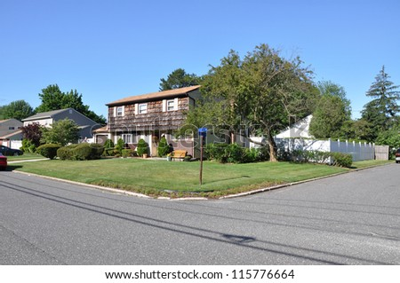 Suburban Neighborhood Corner High Ranch Style Home in residential district on sunny blue sky day - stock photo