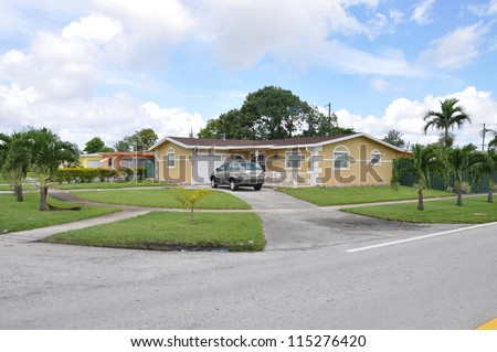 Suburban Neighborhood Corner Ranch Style House Palm Trees Car parked in driveway blue sky clouds day - stock photo