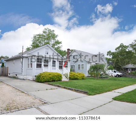 Suburban Neighborhood Cottage Bungalow Style Home Sidewalk and Driveway in Residential District Blue Sky Clouds - stock photo