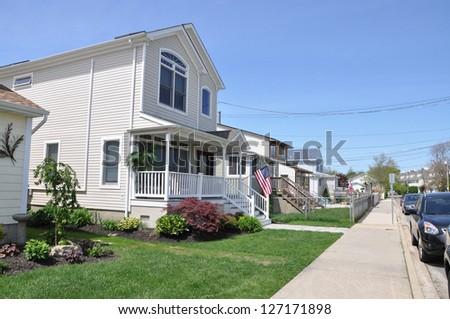 Suburban Neighborhood Homes American Flag Cement Sidewalk - stock photo