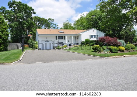 Suburban Ranch Style Architecture Home Blacktop Driveway Landscaped front yard lawn sunny blue sky day with clouds - stock photo
