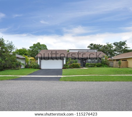 Suburban Ranch Style Home Blacktop Driveway One Car Garage landscaped Front Yard Lawn