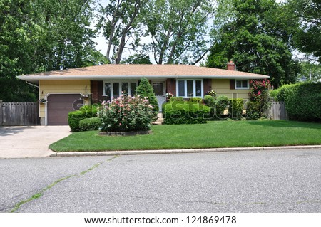 Suburban Ranch Style Home Landscaped with flowers and hedges - stock photo