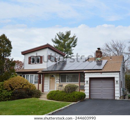 Suburban Ranch style home with solar panel on roof residential neighborhood USA blue sky clouds - stock photo