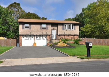 Suburban Ranch Style Two Car Garage Home Mailbox on Curb Sunny Day - stock photo