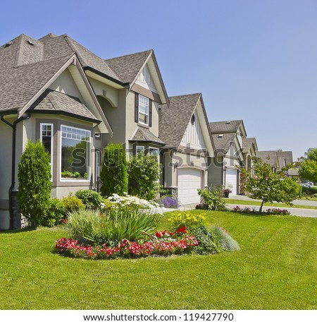 Suburban residential street with landscape on the front and blue sky background - stock photo