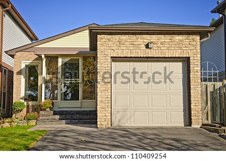 Suburban small bungalow house with single garage - stock photo