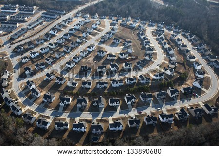 Suburban sprawl housing track in late afternoon light. - stock photo