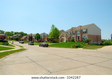 Suburban street and homes in the summertime.