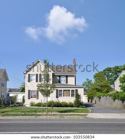 Suburban Two Story Home on Residential Neighborhood Street Sunny Blue Sky Day Cloud