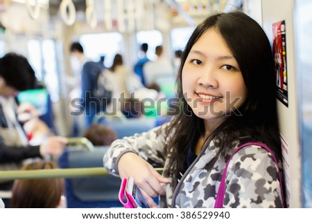 Subway commuter woman on Japanese public transport in osaka, Japan. Tourist using Japan's capital city metro system to commute. Portrait of happy asian lady holding smartphone. - stock photo