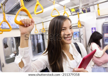 Subway commuter woman on Japanese public transport in Tokyo, Japan. Tourist using Japan's capital city metro system to commute. Portrait of happy asian lady holding handhold inside the wagon. - stock photo