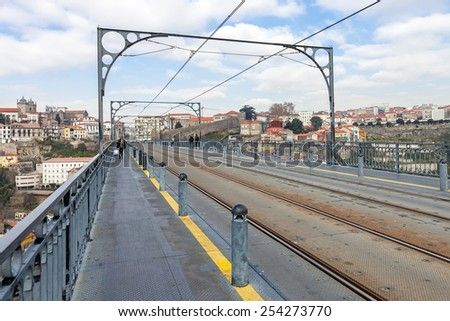 Subway railway tracks and electric cables on the superior deck of the Dom Luis I bridge connecting Vila Nova de Gaia to the city of Porto, seen in the background, over the Douro River - stock photo