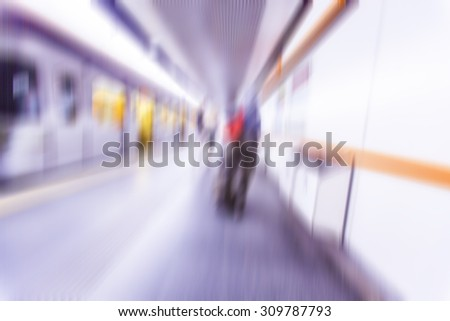 subway train in metro station with motion blurred people walking