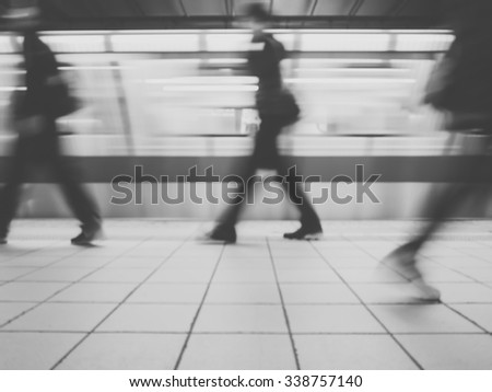 Subway train leaving station. People coming to or leaving the platform. Motion blur. City life.Black and white image. - stock photo