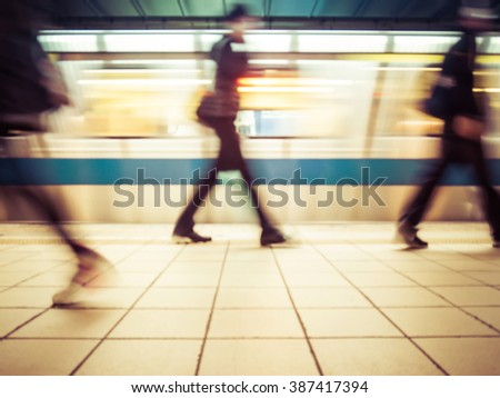 Subway train leaving station. People coming to or leaving the platform. Motion blur. City life.Toned image. - stock photo