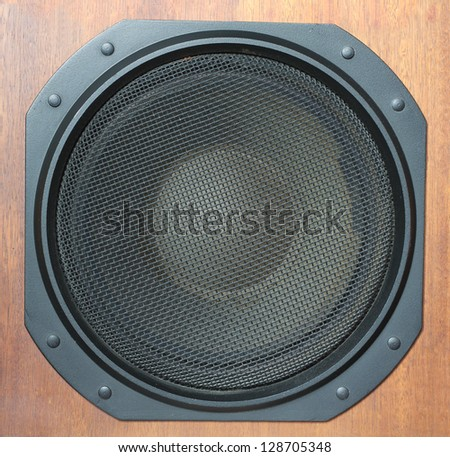 Subwoofer Loud speaker system with round black grill and wooden finish closeup