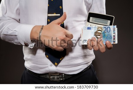 Succesfull Businessman in nice suit showing OK by his hands. Successful businessman with  euro money and calculator in his hands. - stock photo