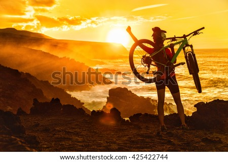 Success, achievement, accomplishment and winning concept with cyclist mountain biking. Happy MTB woman cycling raising arms lifting bike by sea during sunset cheering and celebrating at summit top. - stock photo