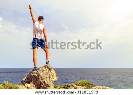 Success achievement climbing, running or hiking accomplish business concept with man celebrating with arms up raised outstretched. Successful hiker, climber or trail runner inspirational landscape - stock photo