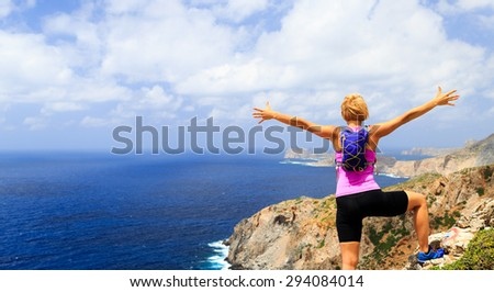 Success achievement running, climbing or hiking accomplishment concept, woman celebrating with arms up raised outstretched hiking, climbing or trail running healthy lifestyle - stock photo
