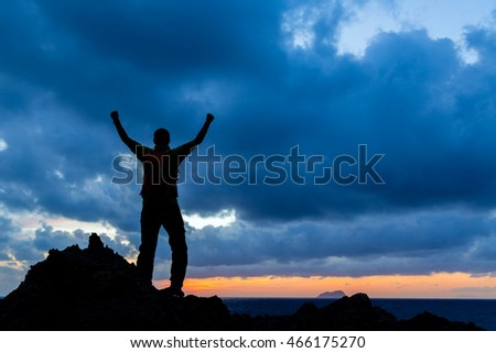 Success achievement running or hiking accomplishment. Business concept with man celebrating with arms up raised outstretched hiking, climbing, running outdoors. Motivation and inspiration in nature.