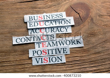 Success  acronym in business concept, words on cut paper on wooden background - stock photo