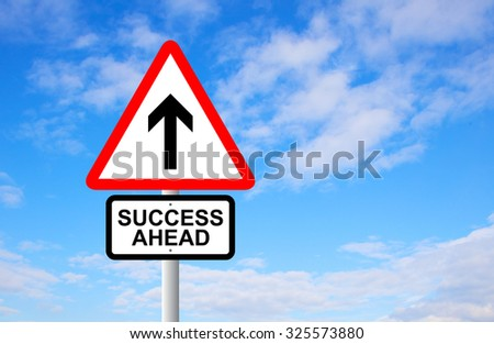 Success ahead and arrow sign post against blue sky
