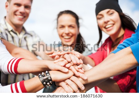 success and gesture concept - close up of teenagers hands on top of each other outdoors - stock photo