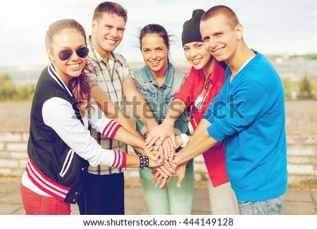 success and gesture concept - group of smiling teenagers with hands on top of each other outdoors