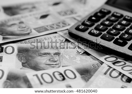 Success and got profit from business with a new series of Swedish kronor currency,money and calculator,Focus on eye of a man on banknotes with black and white color