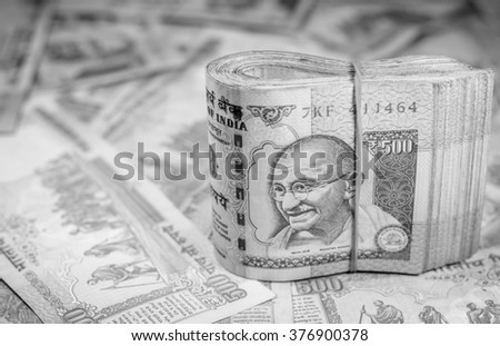 Success and got profit from business with 500 banknotes of indian rupee currency,money on black and white color,Focus on eye of Gandhi
