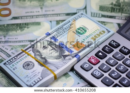 Success and got profit from business with many one hundred american dollar currency,money with calculator,Focus on eye of Franklin - stock photo