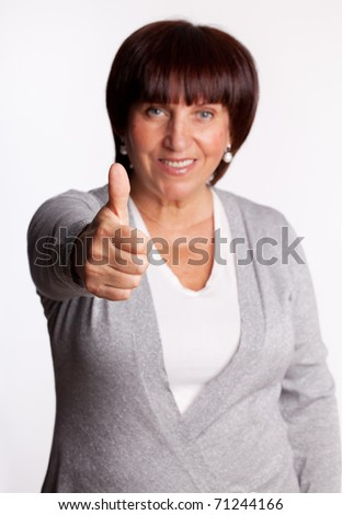 Success and happy mid adult woman. Focus on hand - stock photo